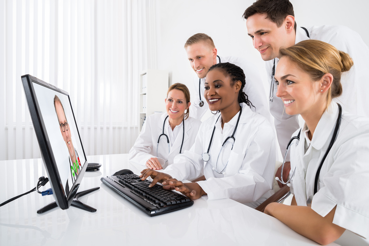 Group Of Doctors Videoconferencing On Computer In Hospital With a Healthcare CRM