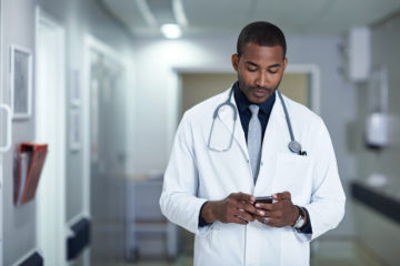 Cropped shot of a doctor using his cellphone increasing patient engagement by texting a patient