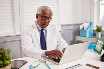 Senior black male doctor in white coat integrating automated Healthcare CRM on a laptop in his office