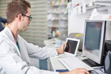 Shot of male pharmacist sitting at his desk and working with digital tablet and computer to improve patient engagement