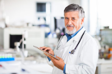 Senior doctor using his tablet computer at work with Healthcare CRM software