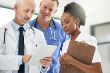 Cropped shot of a doctor showing his colleagues a patient file on his digital tablet with healthcare crm