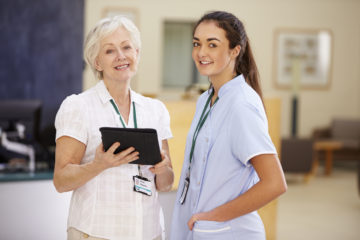 Female Consultant In Meeting With Nurse Using Digital Tablet Looking At Camera Smiling. Patient Support