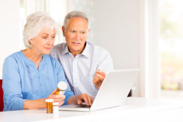Senior couple with prescription pill bottles using healthcare CRM on laptop at home. Horizontal shot.