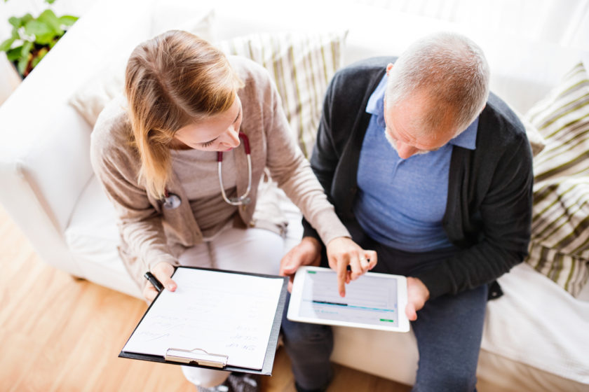 Doctor and senior man during home visit. A female nurse or a doctor showing test results on a tablet. High angle view. Patient engagement Healthgrid concept