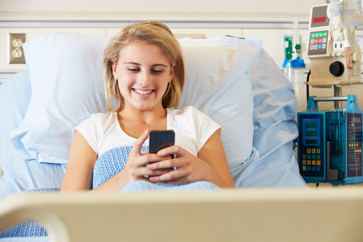 young girl in hospital bed using cellphone to look at new media