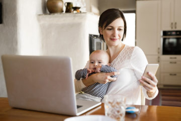 Beautiful mother at home with her cute baby son in her lap, sitting at the kitchen table, working on laptop, holding smart phone checking with a healthcare crm app