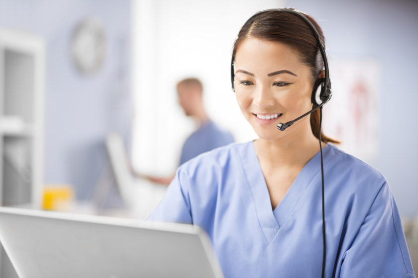Healthcare CRM concept. A young female nurse talks into a headset . She is wearing medical scrubs and looks to camera chatting on the phone. In the background we can see a blurred clinic .