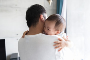 Father holds crying baby with Psoriasis