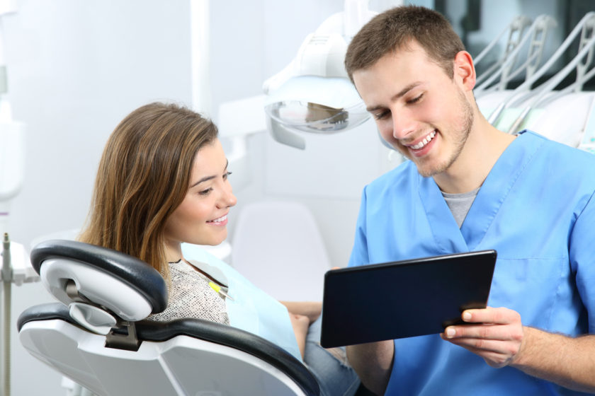 Happy dentist and patient commenting treatments in a tablet application in a consultation with medical equipment in the background. Patient Engagement concept